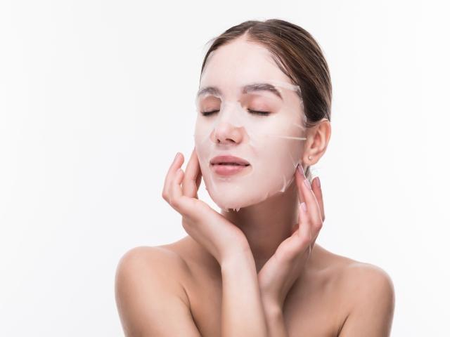 Dbanie o skórę od młodości pozwoli nam przesunąć czas powstawania zmarszczek. Na zdjęciu kobieta nakłada maseczkę w płachcie na twarz.