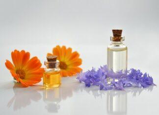 Na zdjęciu dwie buteleczki zawierajace olejki kosmetyczne, w otoczeniu kwatów