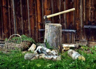 Na zdjęciu siekiera uniwersalna wbita w kołek do rąbania drewna, poniżej leżą porąbane szczapy.