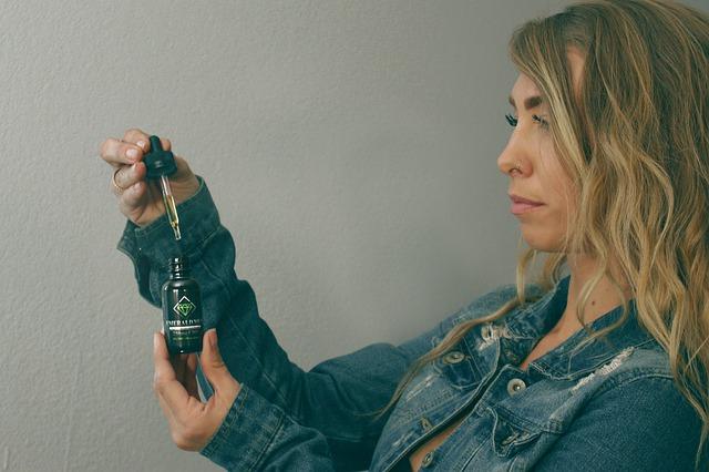 Olejki kosmetyczne powinny być odpowiednio przechowywane. Na zdjęciu kobieta z buteleczka oleju konopnego, w ciemnym szkle i z pipetą.