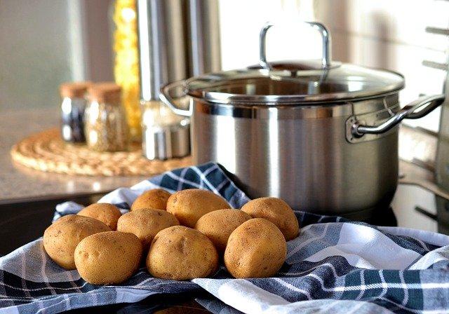 Jak wybrać ziemniaki na idealne frytki? Na zdjęciu umyte ziemniaki na ścierce. W tle przygotowany garnek do ich ugotowania.