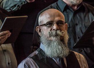 Aby osiągnąć tak pięknie wystylizowaną brodę i wąsy należy użyć odpowiednich kosmetyków do brody. Na zdjęciu mężczyzna z długą siwą brodą oraz finezyjnie wywiniętymi wąsami.