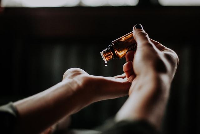 Olejowanie włosów poprawia ich kondycję. Na zdjęciu kobieta trzyma buteleczkę olejki, kropla opada jej na dłoń. Jest to poprawna metoda aplikacji olejku.