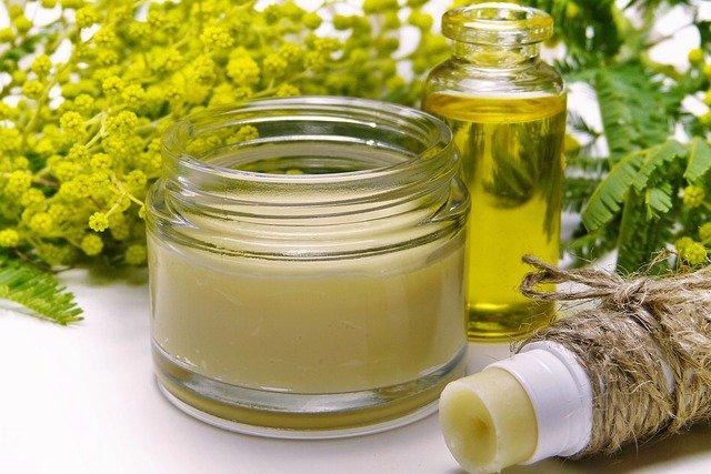 Woski do brody często sprzedawane są w słoiczkach, by łatwo można się dostać do zawartości. Na zdjęciu słoiczek z kremem/balsamem oraz buteleczka olejku i pomadka. W tle kwiaty.