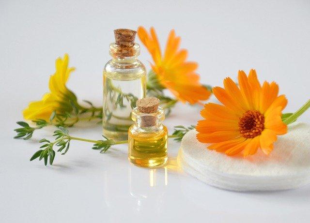 Olejki do olejowania włosów opierają się w głównej mierze na dobroczynnych właściwościach olejków roślinnych. NA zdjęciu diwe buteleczki olejków roślinnych, w tym nagietkowy oraz kwiaty nagietka.