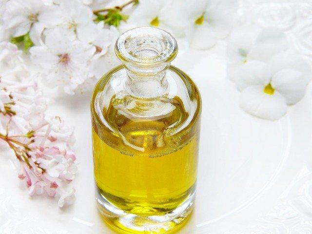 Oczyszczanie twarzy olejkiem - rewolucyjna metoda wprost z Azji. Na zdjęciu olejek w buteleczce na białym tle w otoczeniu lilaku i kwiatów jabłoni.