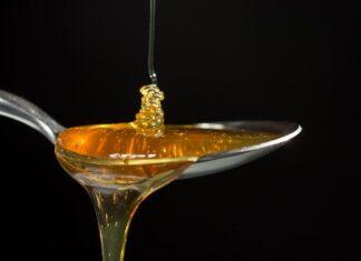 Właściwości miodu są bardzo różne, jednak wiele z nich ma prozdrowotny charakter. Na zdjeciu łyżka pełna miodu, na którą miód leje sie od góry oraz powoli ścieka w dół.