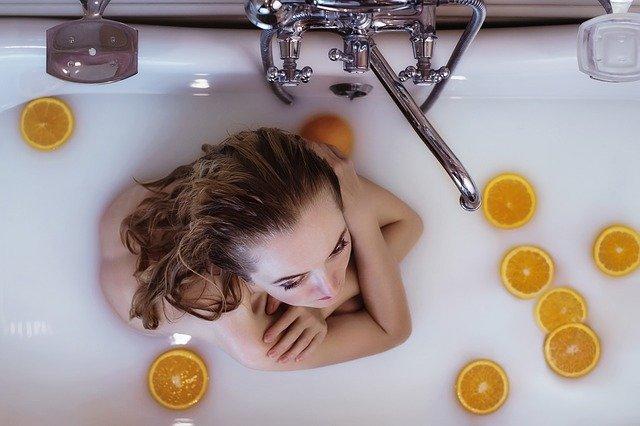Kąpiel w mleku to bardzo dobra opcja dla osób z suchą skórą. Wystarczy kilka filiżanek by stworzyć idealną proporcję. Na zdjęciu kobieta w wannie z mleczną wodą i plastrami pomarańczy.