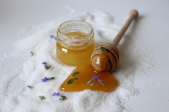 Domowe sposoby na oczyszczanie twarzy to między innymi peeling na bazie miodu. Na zdjęciu słoiczek peelingu w otoczeniu rozsypanego cukru, płatków kwiatów oraz miodu.