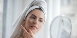 Olejowanie włosów to prosta metoda regeneracji włosów. Na zdjęciu kobieta przegląda się w lusterku, włosy ma owinięte ręcznikiem.