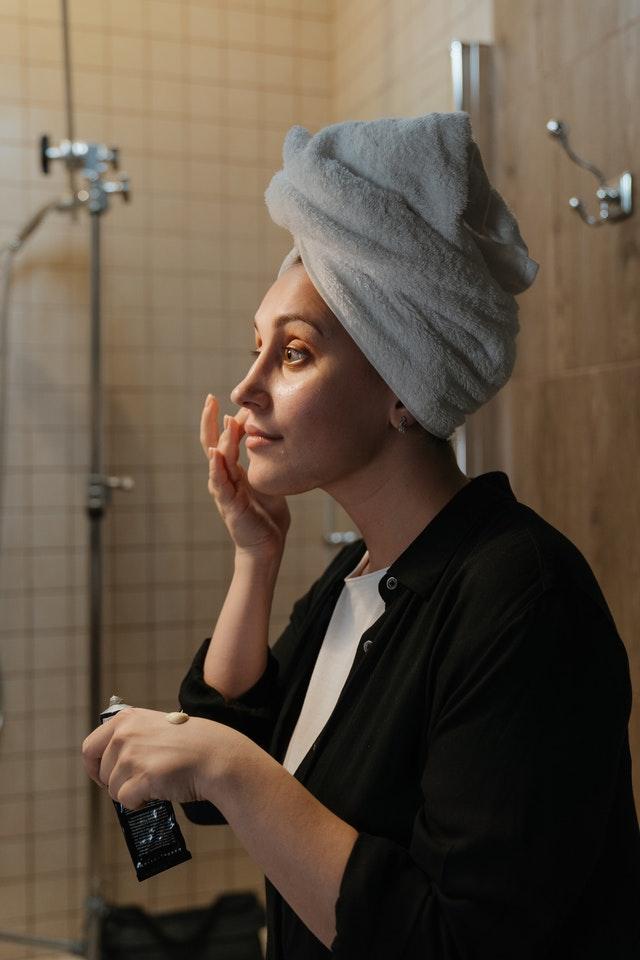 Krem na noc warto stosować w trakcie wieczornej rutyny - na zdjęciu kobieta w czarnej koszuli z białym ręcznikiem na włosach w łazience wciera krem w twarz.