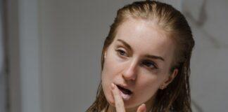 Kobieta w szlafroku wykonuje peeling ust cukrem, czy to dobra metoda?