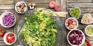 Dieta wegańska opiera się w głównej mierze na świeżych warzywach i owocach, jednym z podstawowych jej potraw są sałatki. Na zdjeciu mamy miskę sałaty oraz różne dodatki do niej takie jak maliny, jagody, pomidory, winogrono, orzechy i grzyby.
