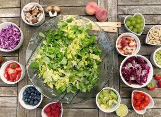 Witarianizm opiera się w głównej mierze na świeżych warzywach i owocach, jednym z podstawowych jego potraw są sałatki. Na zdjeciu mamy miskę sałaty oraz różne dodatki do niej takie jak maliny, jagody, pomidory, winogrono, orzechy i grzyby.