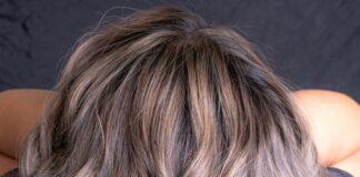 Różne rodzeje włosów potrzebują różnej pielęgnacji. Na zjęciu kobieta prezentuje swoje długie, kręcone farbowane na szaro włosy.