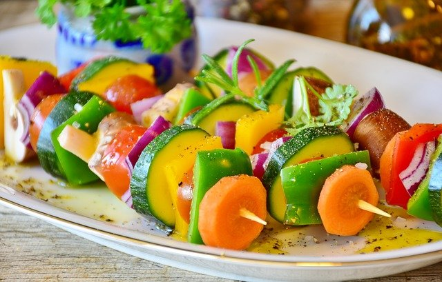 Weganie często chwalą się, że ich dieta jest pełna kolorów, na zdjęciu przykad - wielokolorowe szaszłyki z różnych warzyw: marchewki, papryki, cukinii, kabaczka.