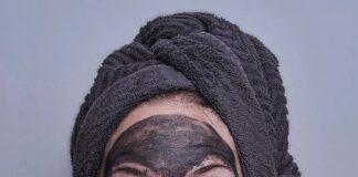 Kobieta w maseczce z węgla aktywnego - to jeden ze sposobów na oczyszczanie twarzy domowym sposobem.