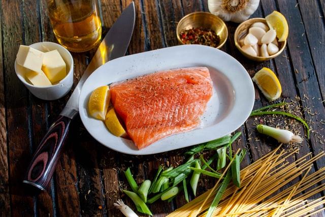 Dieta paleo zakłada duże spożycie ryb oraz tłuszczy. Na zdjęciu płat łososia na półmisku, w otoczeniu przypraw i oliwy.