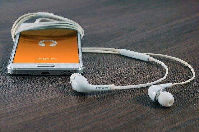 Jak wybrać nowy telefon? To nie łatwe zadanie! Na zdjęciu telefon marki Samsung, leżący na blacie wraz z słuchawkami.
