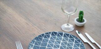 Post przerywany to świetna metoda odchudzania, która ma sporo zalet, ale również wady. NA zdjęciu pusty talerz, nakryty stół do posiłku.